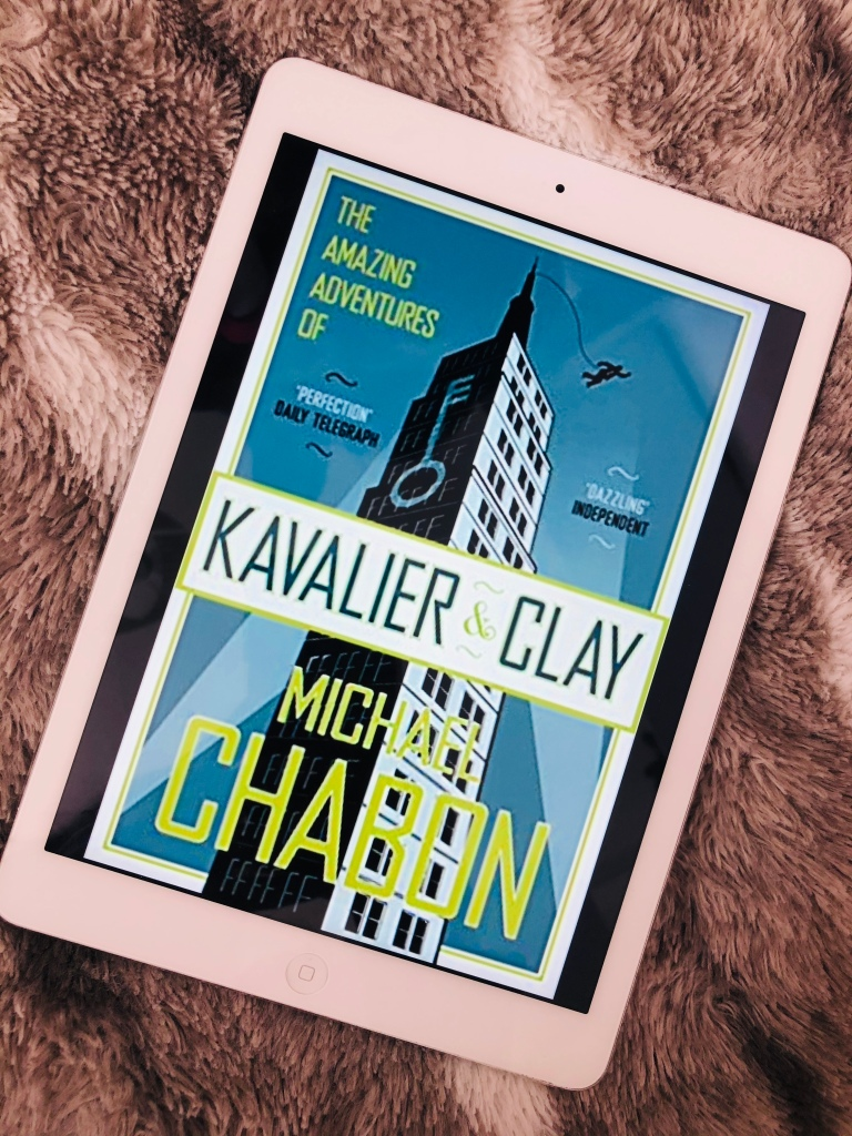 The cover image of the book on an iPad, adopt a furry blanket. The cover shows a comic style Empire State Building with a key on one side, and a figure jumping from the top, attached to a chord.